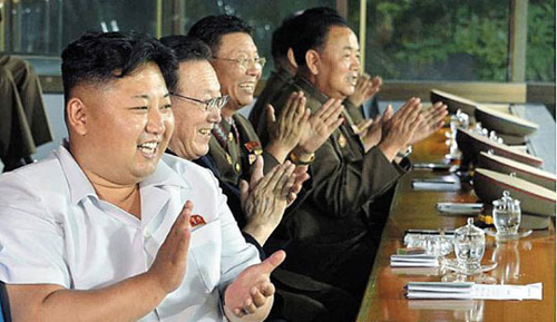 North Korean leader Kim Jong-un (far left) claps while watching a soccer match in Pyongyang, in this photo released by Rodong Sinmun on Sunday. Next to Kim is Kim Yang-gon, the director of the United Front Department in charge of inter-Korean relations.