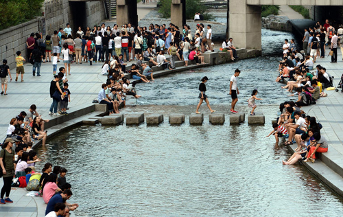 People cool off in the Cheonggye Stream in Seoul on Saturday. /Newsis