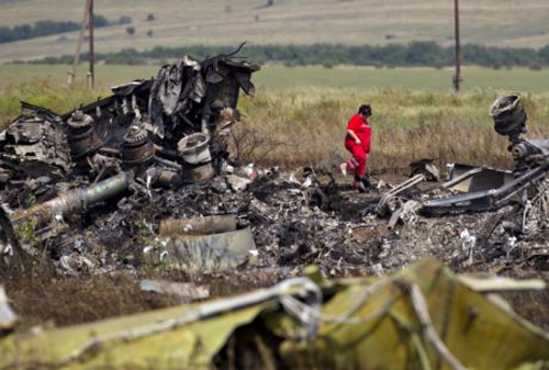 A paramedic walks in charred debris at the crash site of Malaysia Airlines Flight 17 near the village of Hrabove, eastern Ukraine on July 20, 2014. /AP