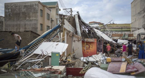 People clear debris after Typhoon Rammasun hit Zhanjiang, Guangdong province, China on July 20, 2014. /Reuters