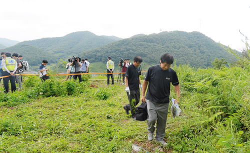 Crime scene investigators on Tuesday collect bones and hair at the site where the body of fugitive ferry owner Yoo Byung-eon was found in Suncheon, South Jeolla Province.