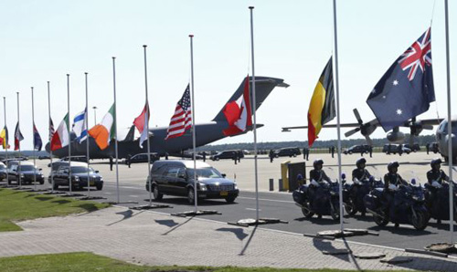The convoy of hearses with the remains of the victims of Malaysia Airlines MH17 downed over rebel-held territory in eastern Ukraine, drives past international flags as it leaves Eindhoven airport to a military base in Hilversum, Netherlands on July 23, 2014. /Reuters