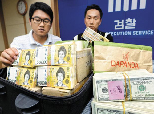 Investigators on Wednesday show cash found at the cottage in Suncheon, South Jeolla Province. /News 1
