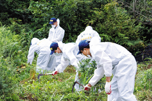 Police on Wednesday search the scene where the body of ferry owner Yoo Byung-eon was found. /Newsis