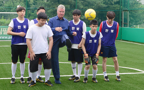 Guss Hiddink (center) tosses a football during the opening ceremony for a futsal field for visually impaired children at Duksung Womens University in Seoul on Thursday. /Newsis