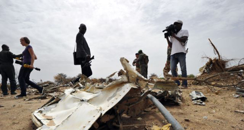 Journalists look at debris at the crash site of the Air Algerie Flight AH 5017 in Malis Gossi region, west of Gao, on July 26, 2014. /AFP