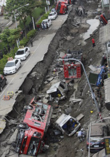 Vehicles are left lie in a destroyed street following multiple explosions from an underground gas leak in Kaohsiung, Taiwan on Aug. 1, 2014. /AP