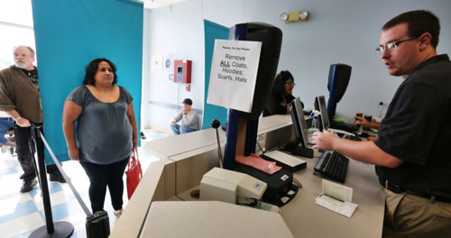 Immigrant and longtime resident in the United States Rosalva Mireles, left, is photographed and processed for her permanent drivers license at a Department of Motor Vehicles office, in Denver on Aug. 1, 2014. /AP