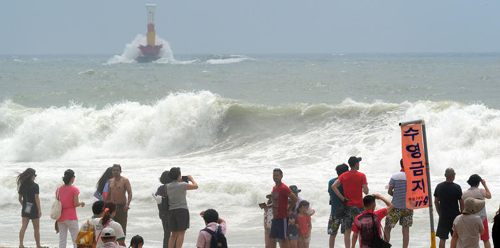 Vacationers watch waves on Haeundae Beach in Busan on Sunday. /Newsis