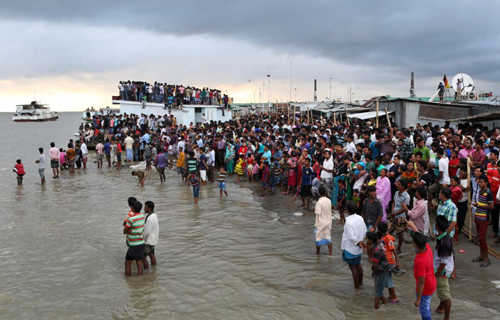 People gather on the banks of the River Padma after a passenger ferry capsized in Munshiganj district, Bangladesh on Aug. 4, 2014. /AP