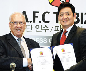 Sportizen CEO Shim Chan-koo (right) shakes hands with A.F.C. Tubize chairman Raymond Langendries during a signing ceremony in Seoul on Monday. /Newsis