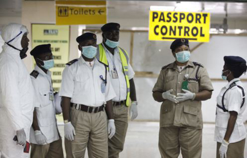 Nigeria health officials wait to screen passengers at the arrival hall of Murtala Muhammed International Airport in Lagos, Nigeria on Aug. 4, 2014. /AP