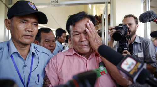 Soum Rithy (center), who lost his father and three siblings during Khmer Rouge regime, is escorted as he cries after the verdict was delivered in the trial of two elderly Khmer Rouge leaders in Phnom Penh on Aug. 7, 2014. /Reuters