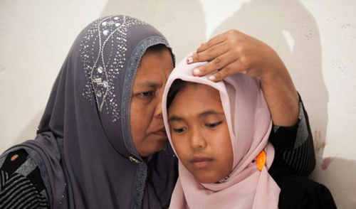 Indonesian mother Jamaliah (left) hugs her daughter Raudhatul Jannah (R) after they were reunited in Meulaboh, Aceh province on Aug. 7, 2014. /AFP