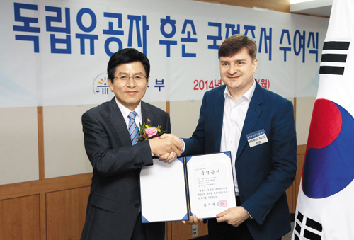 David Jonathan Linton (right) shows a certificate identifying him as a Korean national.