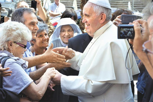 Pope Francis shake hands with Catholics as he visits Jesuit headquarters in Rome on July 31. /AP-Newsis