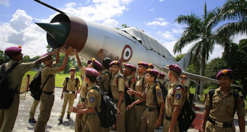 Students gather by an inactive fighter aircraft on display at a Sainik School, or military school, in Goalpara, in the northeastern Indian state of Assam on Aug. 8, 2014. /AP