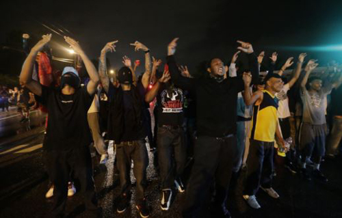 People defy a curfew on Aug. 17, 2014, before smoke and tear gas was fired to disperse a crowd protesting the shooting of teenager Michael Brown last Saturday in Ferguson, Missouri. /AP