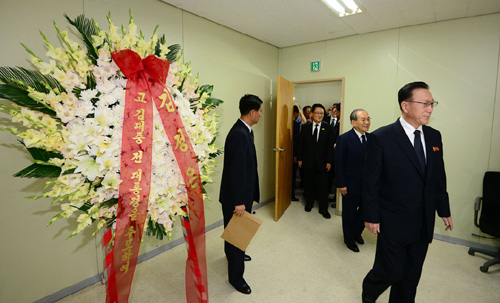 Kim Yang-gon (front), director of the United Front Department of the North Korean Workers Party, and South Korean delegation enter a meeting room in Kaesong on Sunday. On the left is a wreath from North Korean leader Kim Jong-un.