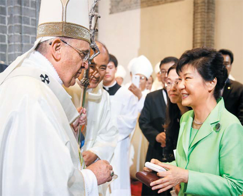 Pope Francis gives a present to President Park Geun-hye after a mass at Myeongdong Cathedral in Seoul on Monday. /Newsis