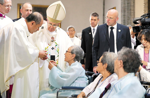 Pope Francis meets with victims of sexual slavery in World War II before a mass at Myeongdong Cathedral in Seoul on Monday. /Newsis