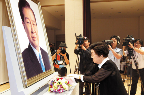 Lee Hee-ho, the widow of former President Kim Dae-jung, offers flowers before Kims portrait during a memorial service at Seoul National Cemetery on Monday.