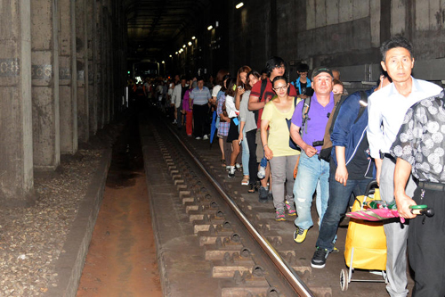 Passengers walk through a tunnel after a blackout caused their train to stop between Jegidong Station and Cheongnyangni Station on Subway Line No. 1 on Tuesday. /Newsis