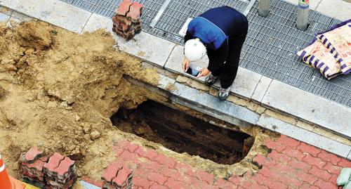 A city official takes a photo of a newly found sinkhole in Songpa, Seoul on Thursday. /Newsis