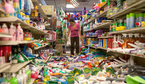 Nina Quidit cleans up the Dollar Plus and Party Supplies Store in American Canyon, California, after a major earthquake on Aug. 24, 2014. /AP