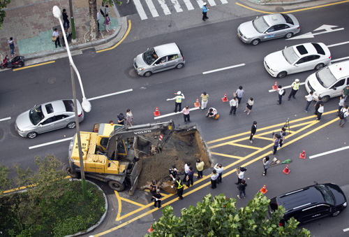 A crane pours soil into a sinkhole in Seocho, Seoul last Friday.