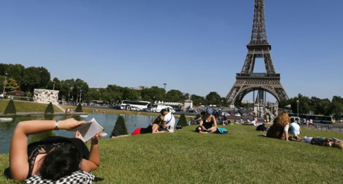 A woman reads a book as she rests in a public garden near the Eiffel Tower on a hot summer day in Paris on July 3, 2014. /Reuters