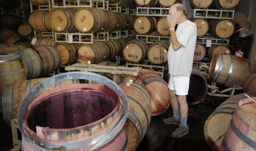 Winemaker Tom Montgomery stands in wine and reacts to seeing damage following an earthquake at the B.R. Cohn Winery barrel storage facility in Napa, California on Aug. 24, 2004. /AP