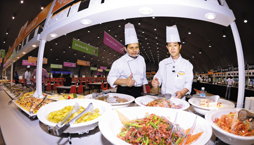 Cooks prepare food in the cafeteria in the athletes village for the 2014 Incheon Asian Games on Tuesday.
