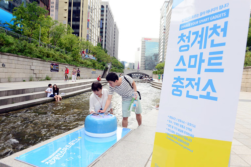 Visitors recharge their mobile phones at a charging booth by the Cheonggye Stream in Seoul on Wednesday. /Newsis