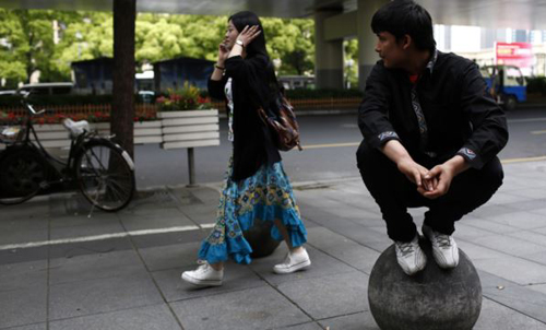 A Uighur man looks at a passing Han woman outside of his restaurant in Shanghai on April 23, 2014. /Reuters