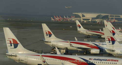 Ground crew work among Malaysia Airlines planes on the runway at Kuala Lumpur International Airport. /Reuters
