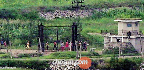 North Koreans pass a guard post near the demilitarized zone on Wednesday.